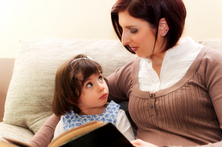 Mother and daughter amuse themselves reading a book in the sofa of house - 2