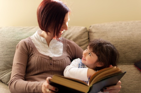 Mother and daughter amuse themselves reading a book in the sofa of house photo