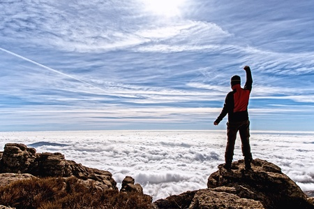 contemplates: Man in the high of the mountain filled with enthusiasm with the impressive panorama that he contemplates