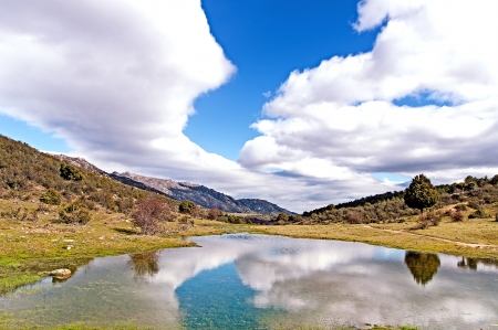 Natural pond in a beautiful mountain valley between the mountains on its clear water reflecting the intense blue sky and thick clouds on a cold winter day Stock Photo - 18135879