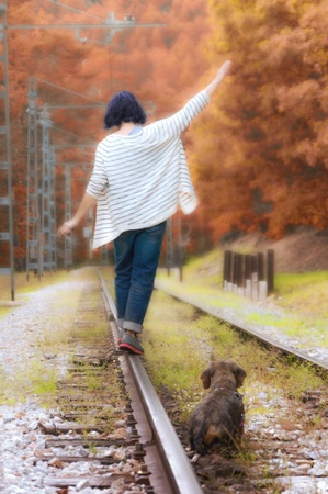 Woman and her pet walk the train tracks deep in a colorful forest in autumn