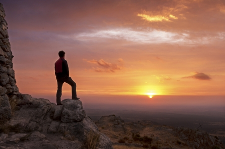 Man on top of a mountain standing contemplates the dawn Stock Photo