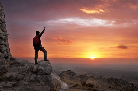 reached: Man on top of mountain with his arms raised to have reached the goal after a great effort admiring the sunrise