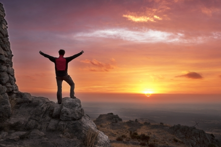 reached: Man on top of mountain with his arms raised to have reached the goal after a great effort admiring the sunrise - 2