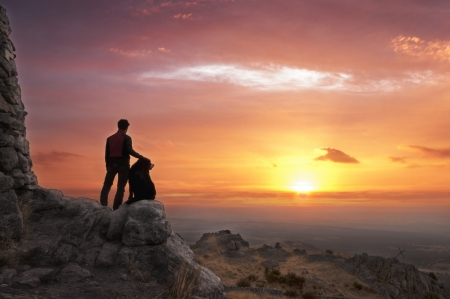 Man and his faithful companion watching the sunrise at the top of the mountain - 2 Stock Photo
