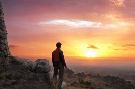 Man on top of a mountain standing contemplates the dawn - 2 Stock Photo
