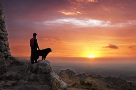 Man en zijn trouwe metgezel kijken naar de zonsopgang op de top van de berg Stockfoto
