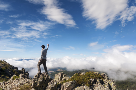 Young man at the top of the mountain contemplate  the beautiful phenomenon of having clouds under your feet photo