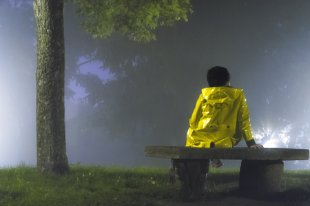 foggy hill: Woman with yellow raincoat sitting on a stone bank on a hill a foggy night in autumn