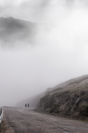 Women walking through the thick foggy mountain road one cold autumn day photo
