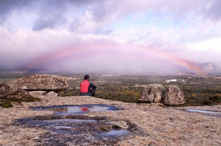 Man sitting on the rocks watching the rainbow after the rain  Stock Photo