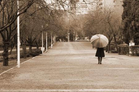 lluvia paraguas: Mujer caminando con el paraguas en el parque en un día de lluvia - Sepia Foto de archivo