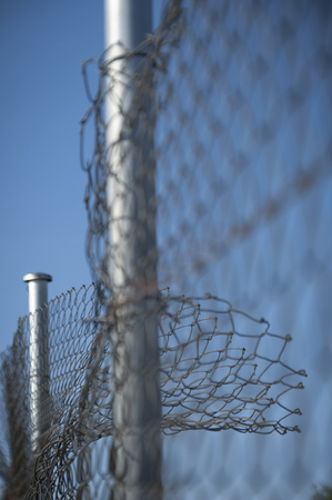 barbwire: Security fence broken and bent wire with blue sky background Stock Photo