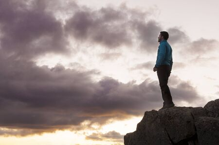 contemplates: Victorious man contemplates the sunset from the top of the mountain Stock Photo