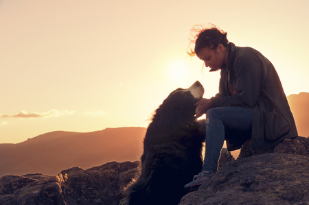 necking: Young woman fondles her pet during a beautiful sunset at the top of the mountain