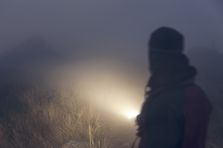 abstract portrait: Abstract portrait man with flashlight in the fog walking through the mysterious forest in the fog