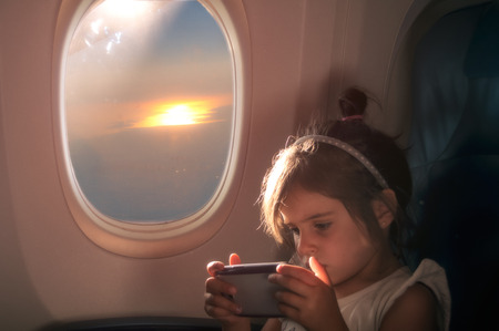 little girl plays with the tablet on the seat of the plane at sunset