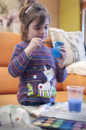 Child having fun painting at home a vase with watercolors