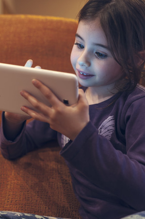 Girl plays with tablet on the sofa at home Stock Photo