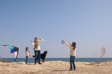 Family playing with kite by the sea