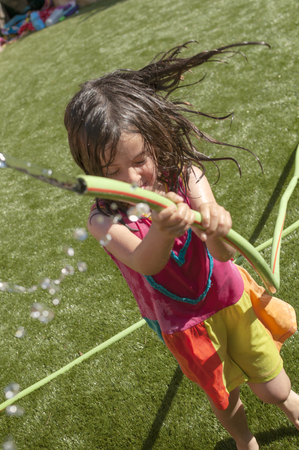 Girl playing in the garden getting wet with the hose a hot summer day