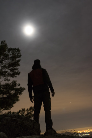 Moonlight man silhouette. He looks at the moon.