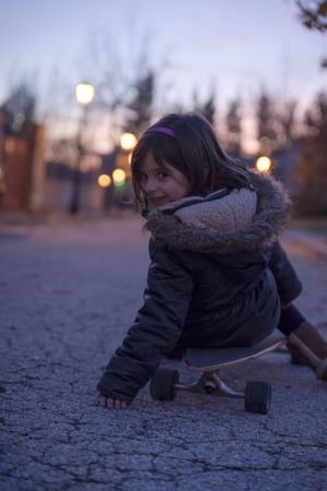 Girls playing with skateboard on the street at sunset