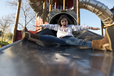 Sisters playing on the park slide Stock Photo