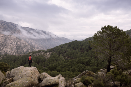Man at the top of the mountain contemplates the beautiful landscape