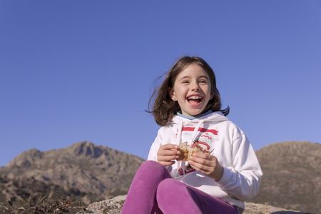 Smiling girl restores strength with a sandwich on the mountain