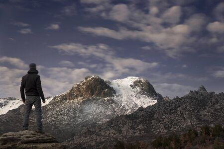 achievment: Man contemplates the last rays of the sun on the snowy mountain at sunset