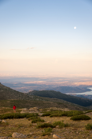Girl climber contemplates from the top of the mountain a amazing sunset and the moonrise. Navacerrada, Spain.