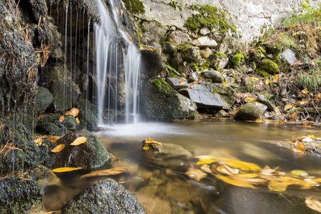 Waterfall on the mountain river in autumn. Long exposure shot. Stock fotó