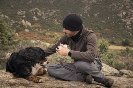Young man sits at the top of the mountain with his dog and a cup of hot drink in his hands. On a cloudy and cold autumn day. Stock fotó