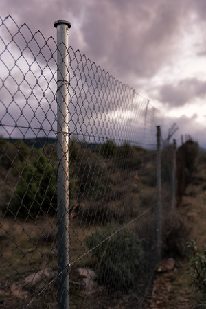 Apocalyptic scene of barbed wire fence and cloudy sky Stock fotó