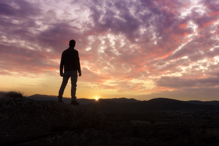 A young man traveler standing  enjoy with beautiful sunset on top of the mountain. Stock fotó