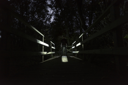 Silhouette of man against the light on the forest bridge on a dark night. Abstract concept Stock fotó