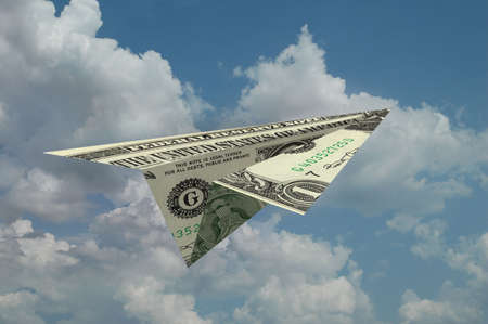 corporate greed: Paper airplane made out of money with clouds in the background Stock Photo