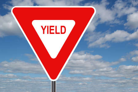 yield: Yield sign with clouds in the background Stock Photo