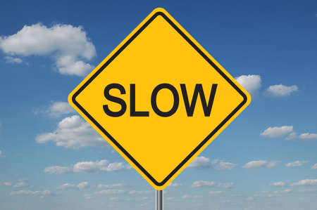 Slow traffic sign with clouds in the background Stock Photo - 566757