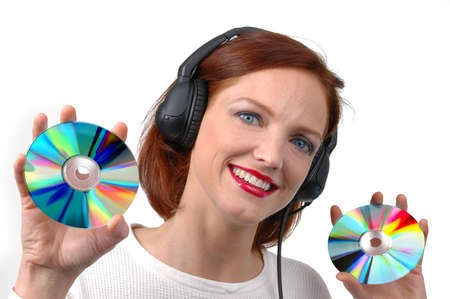 Woman with headphones holding CDs on white background