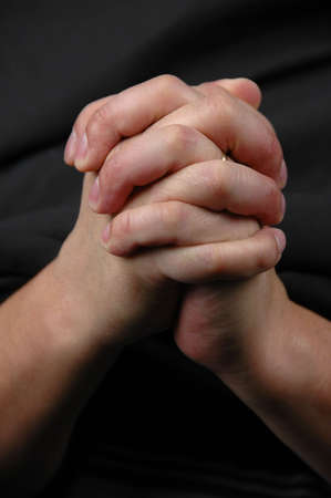 reverent: Hands in prayer on dark background