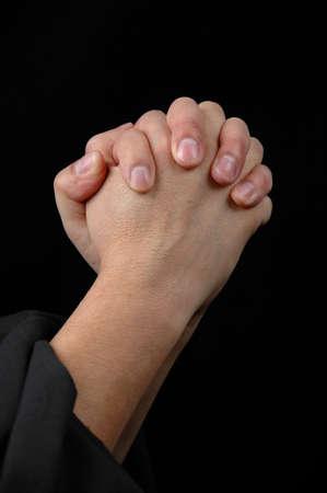 Hands in prayer on dark background photo