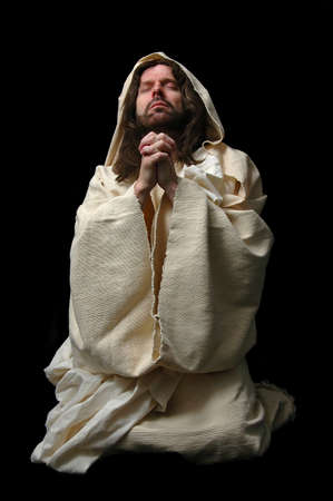 Jesus in prayer on his knees on dark background Stock Photo - 1124999