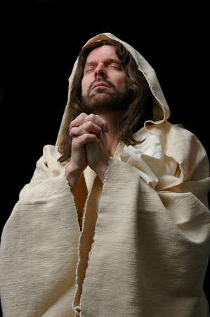 mano de dios: Retrato de Jes�s en rezo con el fondo oscuro Foto de archivo