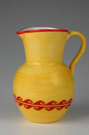 Ceramic jug in yellow and red on neutral background photo