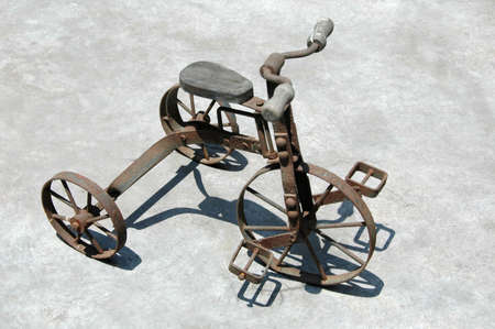 antique tricycle: Antique Tricycle with sharp shadow seating on a concrete surface