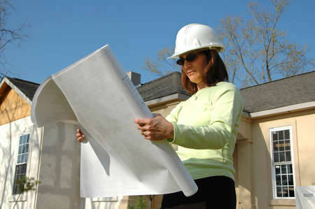 Architect with blueprints and hard hat at site