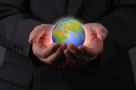 environmentalism: Businessmans hands and earth on dark background