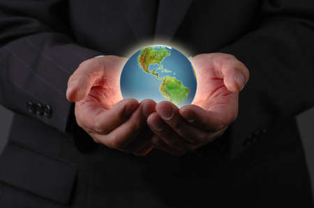 Planet earth in businessmans hands with dark background